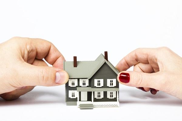 Foto van een plastic huisje, met twee verschillende handen die het huisje vast pakken. Kopen of huren, wat is verstandig voor jou?