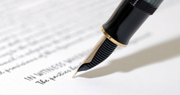 Foto van een pen die een papier ondertekent.