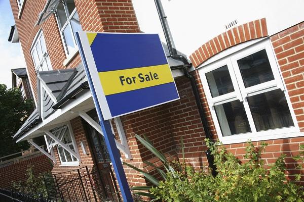 Foto van een huis met een for sale-bord erbij.