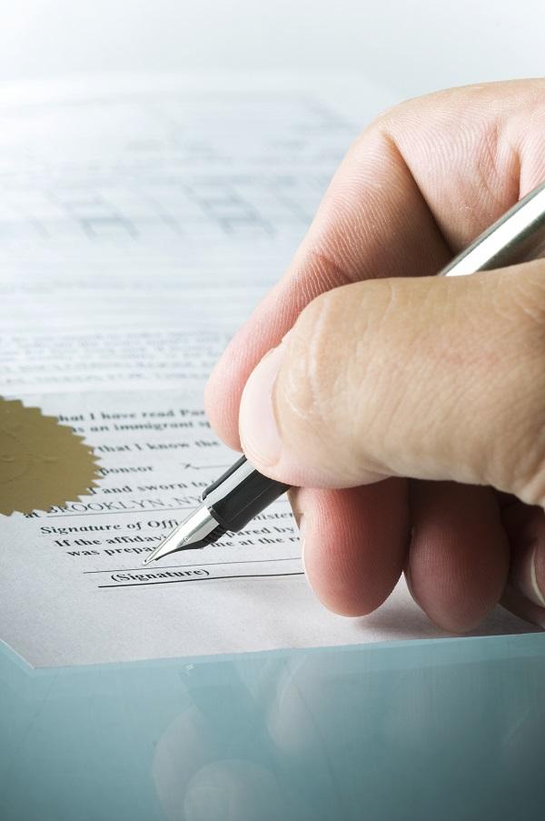 Foto van een hand die een akte ondertekent met een pen.