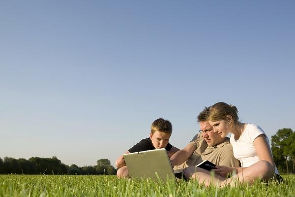 Foto van ouders en kind die in het gras op een laptop aan het kijken zijn