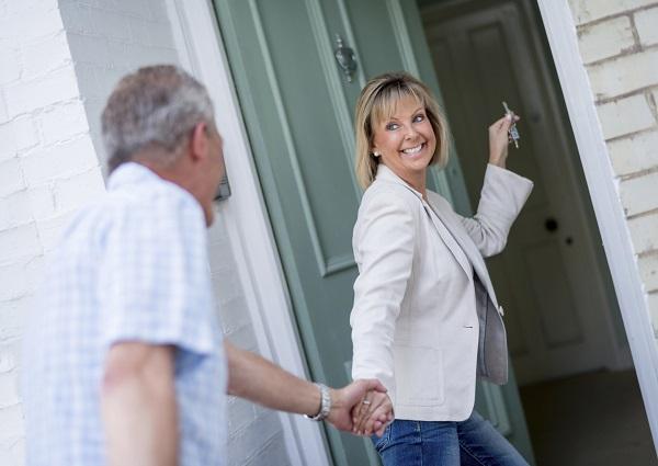 Foto van een stel dat hun droomhuis met de sleutels in de hand naar binnen stapt.