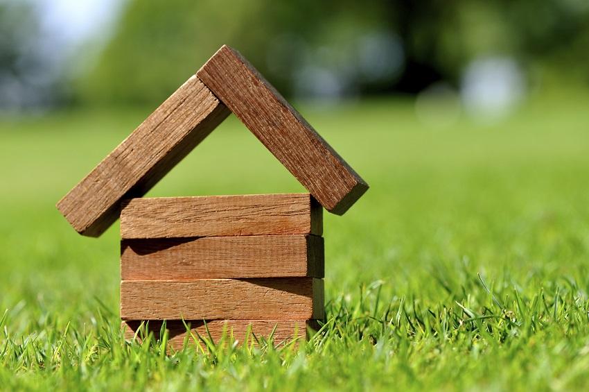 Afbeelding van een houten huisje in het gras