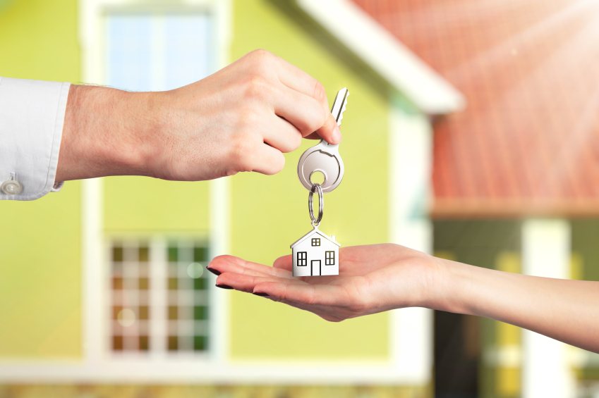 Foto van een sleutel die overhandigd wordt, met een klein huisje als sleutelhanger