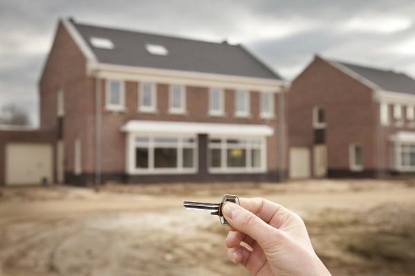 Foto van een woning met op de voorgrond een hand die een sleutel vasthoudt.