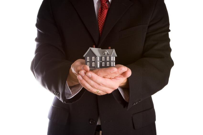 Afbeelding van handen met een huisje erin. Wat maakt een goede aankoopmakelaar? Onderhandelmakelaar Han Busio vertelt.