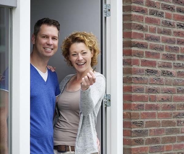 Stel in de deuropening van hun nieuwe woning. Zelf huis kopen zonder aankoopmakelaar?